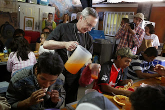 Photo: Auxiliary Bishop Luis R. Zarama of Atlanta serves juice to men at the Aid Center for Deported Migrants in Nogales, Mexico, March 31. Dinner that evening was served by visiting U.S. bishops. The center, run by the Kino Border Initiative, was one stop the bishops made during their tour of the border area near Nogales. (CNS photo/Nancy Wiechec) (April 1, 2014)