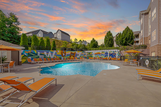 Summit at Cullowhee Apartments community pool with lounge chairs and trees in the background at dusk