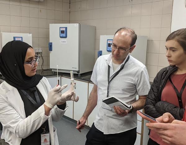 Un grupo de personas que están en un laboratorio médico escuchan a una de ellas hablar sobre pruebas.