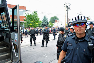 """Photo: Police surround the G20 'Peoples Convergence Space', keeping people in the vacitiy blocked off from onlookers and community members who rallied support of the arrested with chants of """"Whose streets? Our streets!"""""""