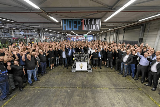 The team of the Mannheim engine plant in Germany, left, follow the one millionth in-line six-cylinder truck engine as it comes off the line. Below: Final inspection of the six-cylinder engine at the plant.