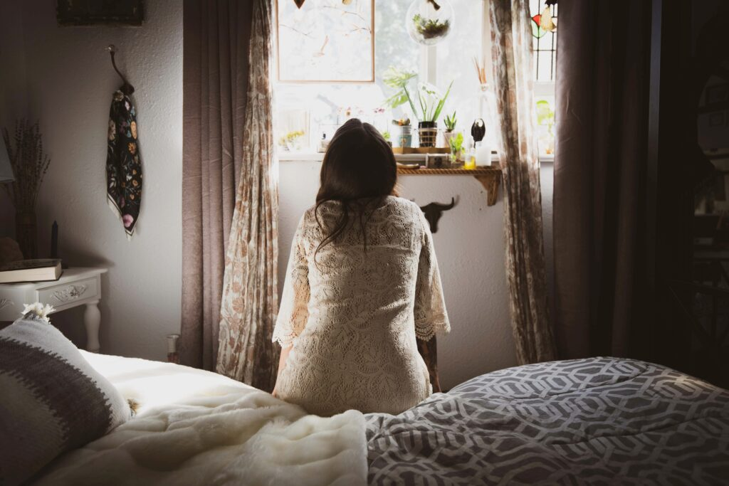 The backside of a woman sitting on the edge of a bed looking out the window while in her bathrobe.