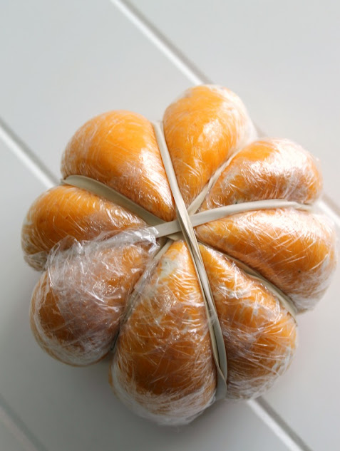 Wrap the cheese ball with plastic wrap and rubber bands to create the pumpkin shaped base for the cheese ball