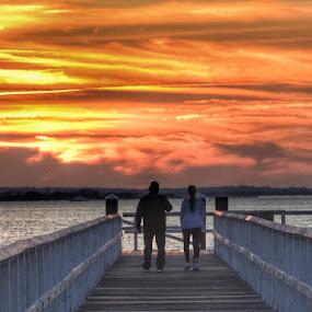 Sharing a moment  by Ann Goldman - Landscapes Sunsets & Sunrises ( water, sunset, cloudscape, pier, couple )