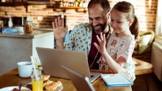 young girl and man waving at laptop screen