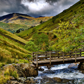 Bridge over a mountain stream by Peter Greenhalgh - Landscapes Mountains & Hills ( clouds, water, uk, stream, cumbria, lake district, wooden bridge, mountains, england, mountain path, hayswater gill, lakeland, river )