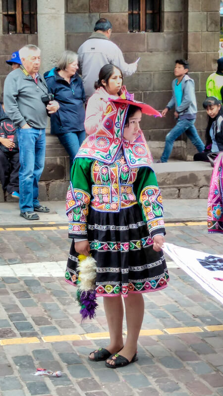 Peruvian girl in traditional peruvian clothes in carnival in cusco at plaza de armas cusco colonial peru south america