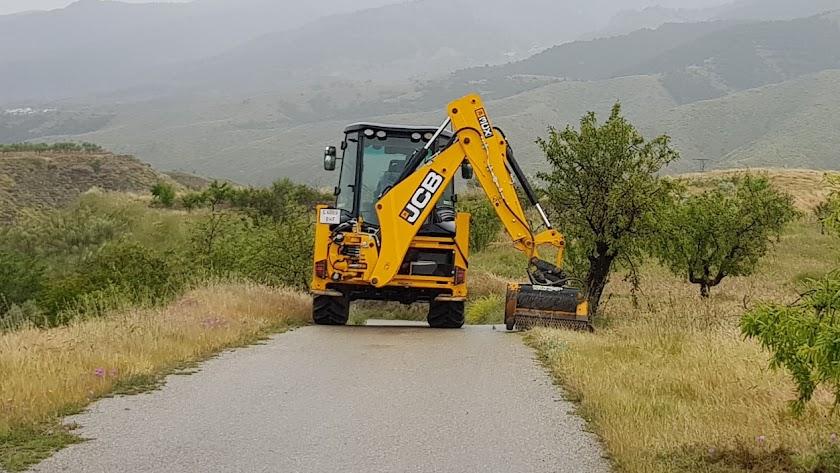 Una máquina excavadora ayuda en las labores de adecuación y limpieza de caminos.