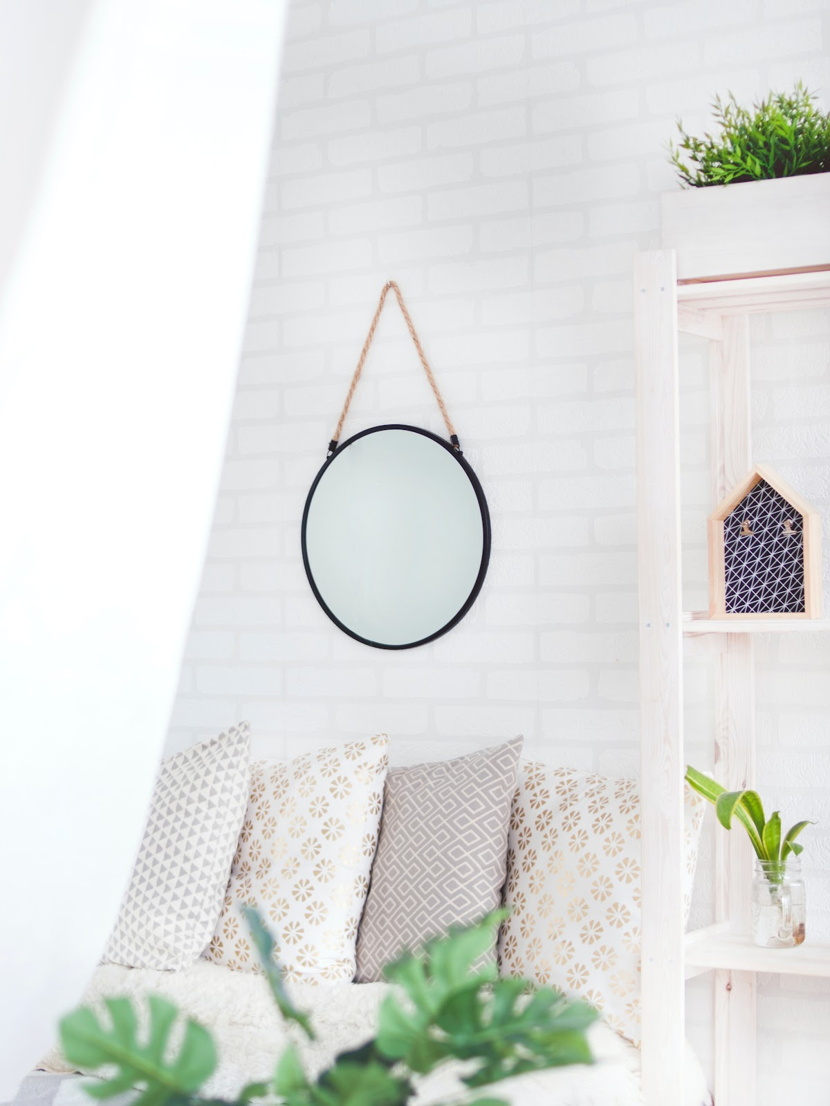 interior design of a condo unit living room with bright white and nude designs and a mirror with black edges hung on a brick-designed wall