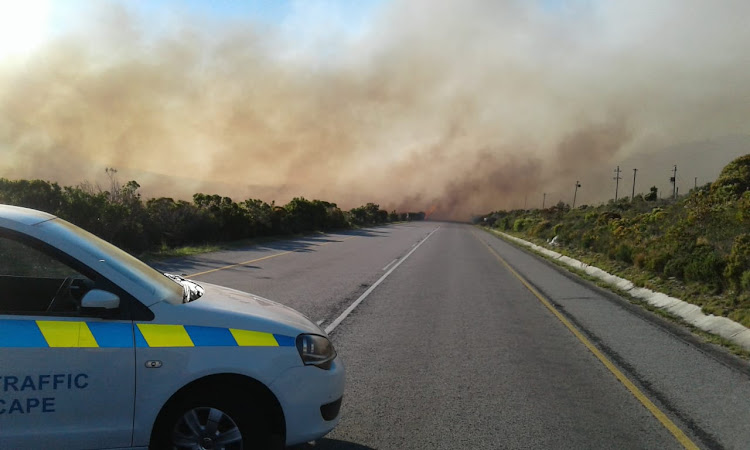The R44 between Gordon's Bay and Kleinmond was closed on Thursday as fire raged on either side of the road.