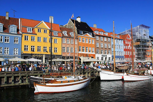 If you find yourself in Nyhavn, a district in Copenhagen, think about buying a beer at a market, then sitting by the quay and watch all the people go by.