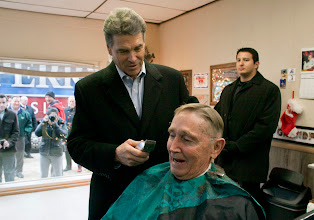 Photo: Republican presidential candidate Rick Perry pretends to cut Leroy Claussen's hair at a barber shop in De Witt, Iowa, on Dec 20. Photo by Nick Oza, The Arizona Republic.