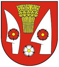Photo: A címer színes rajza, a címer leírása: alul kerekített piros pajzson, fent közepén arany gabonakéve, lejjebb két oldalán ezüst csoroszlyával és ekevassal körbevéve. Az ekevason és csoroszlyán egy-egy arany közepű piros szirmú és zöld kelyhű rózsa látható. Alattuk középen arany közepű ezüst szirmú és zöld kelyhű rózsa van. Az aranyat sárgával, az ezüstöt fehérrel válthatjuk fel.