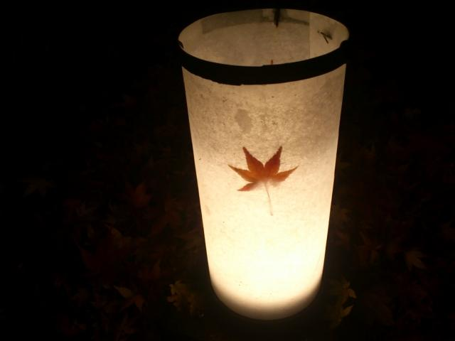 A lighted lantern with an autumn leaf.