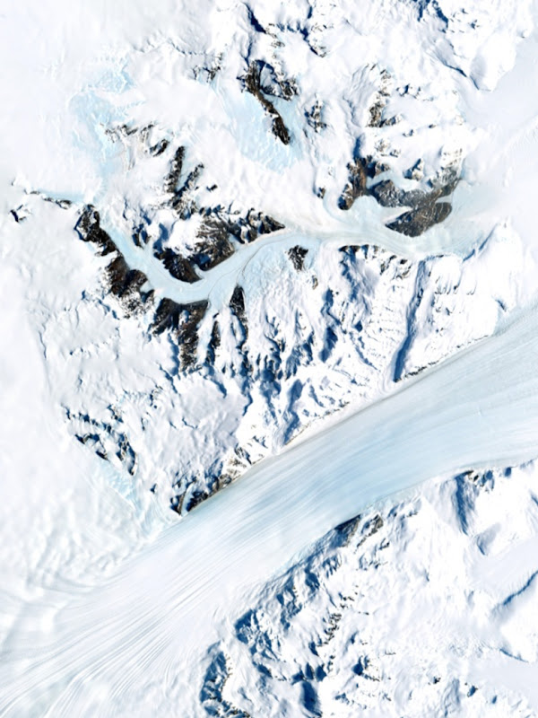 An aerial view of a snowy mountain pass and glacier.