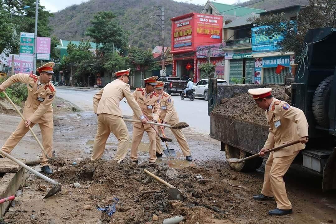 Lực lượng CSGT Kỳ Sơn dọn dẹp bùn đất trả lại mặt đường thông thoáng, an toàn cho người dân.