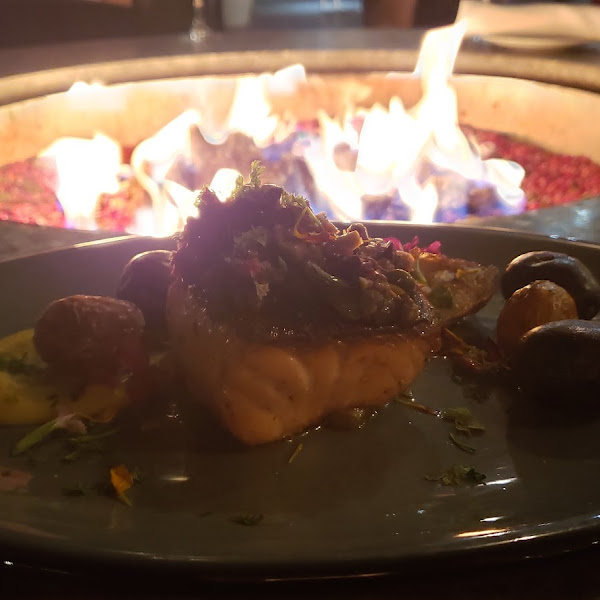 Salmon and potatoes at outdoor fireplace seating