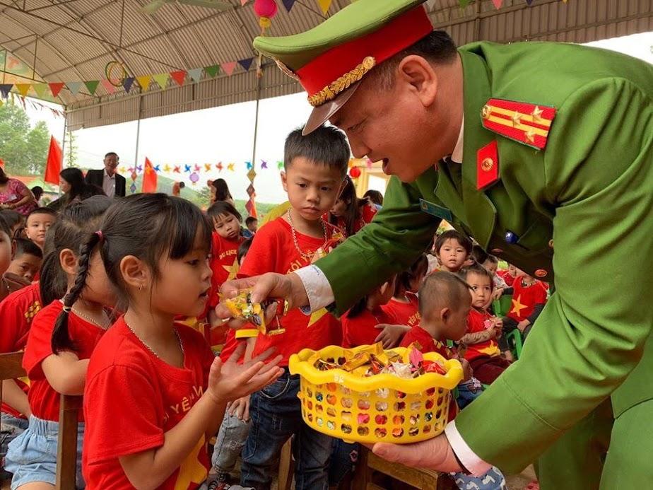 Thượng tá Nguyễn Hồng Tuyến, Trưởng Công an huyện Anh Sơn trao những phần quà cho các em học sinh
