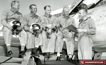 Photo: Left to right that's Gomer Jones, Jack Lauderdale, Eddie Crowder and Wilkinson with Captain David Roberson. It appears the OU coaches are about to get some experience in a military fighter jet.
