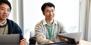 Two men, one wearing glasses, are having a conversation and smiling while working on laptops.