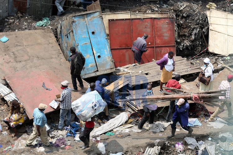 Traders demolish the structures that were left standing after an inferno that consumed Gikomba market stalls on July 14, 2020.