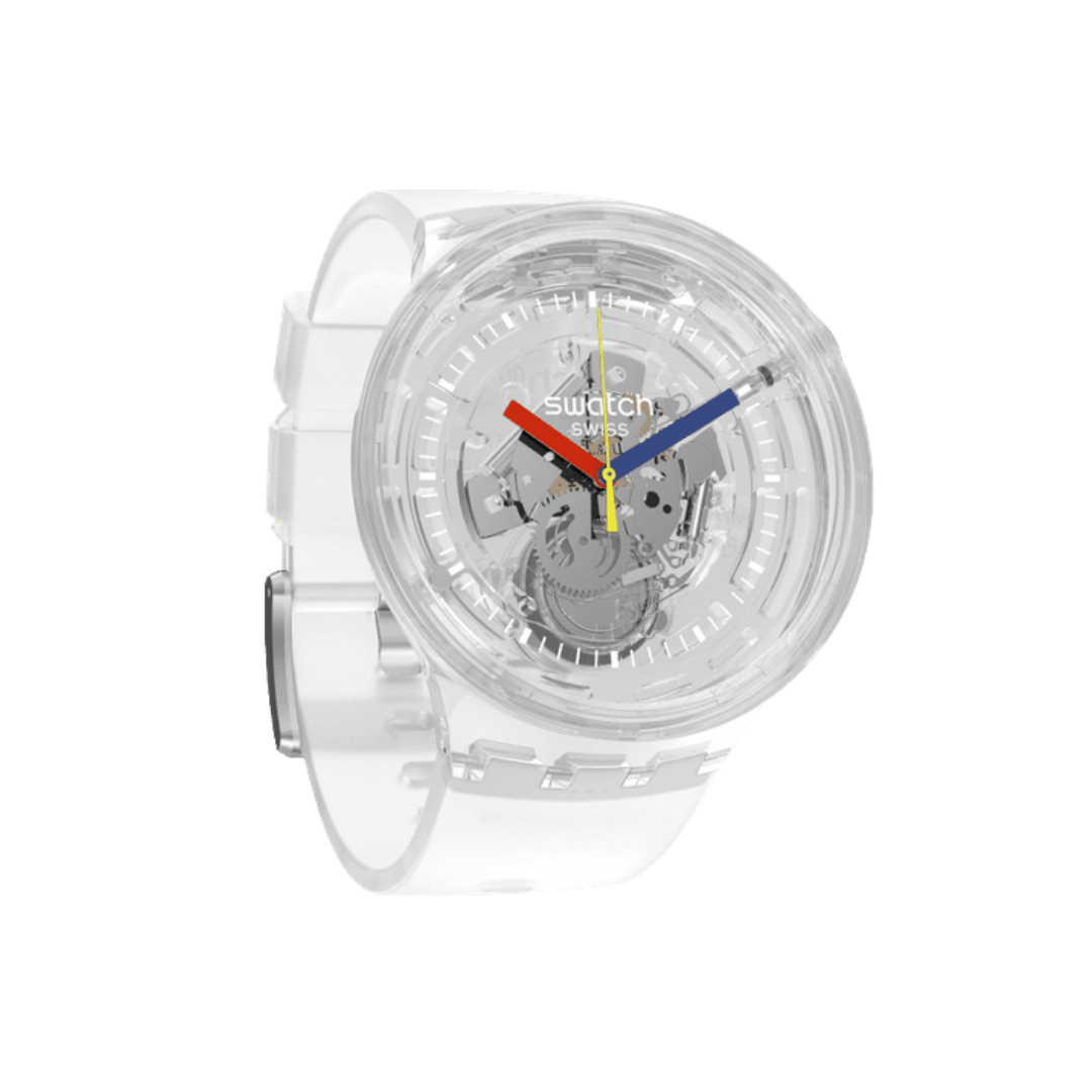 A large clear plastic watch from Swatch. Featuring a skeleton, see through design. Can see the quartz movement. Features red, blue, and yellow hands.