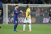 Barcelona's Argentine soccer star Lionel Messi and Hlompho Kekana of Mamelodi Sundowns during the International Club Friendly match between Mamelodi Sundowns and Barcelona FC at FNB Stadium on May 16, 2018 in Johannesburg, South Africa.