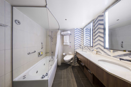 eurodam-Neptune-Suite-Bath.jpg - The bathroom of the Neptune Suite on ms Eurodam features a dual sink vanity and full-size whirlpool bath & shower with additional shower stall.