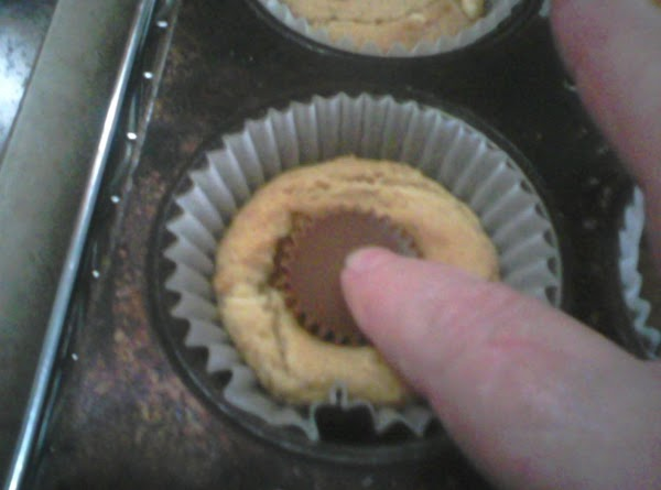 Immediately on taking out, press a minature peanut butter cup in the middle.