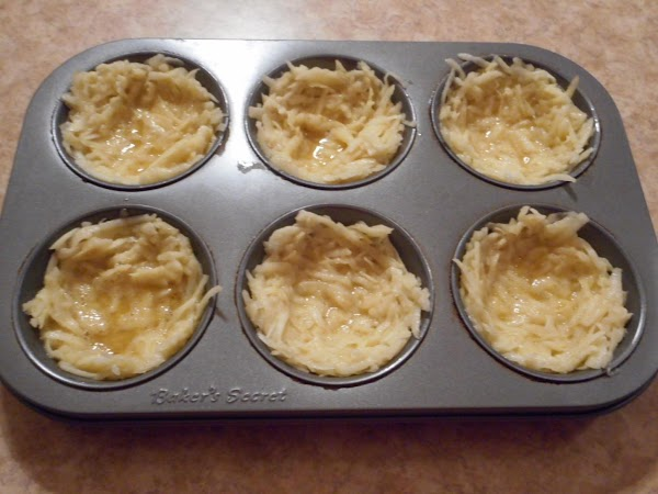 Divide evenly among prepared muffin compartments.  With the back of a teaspoon, firmly...