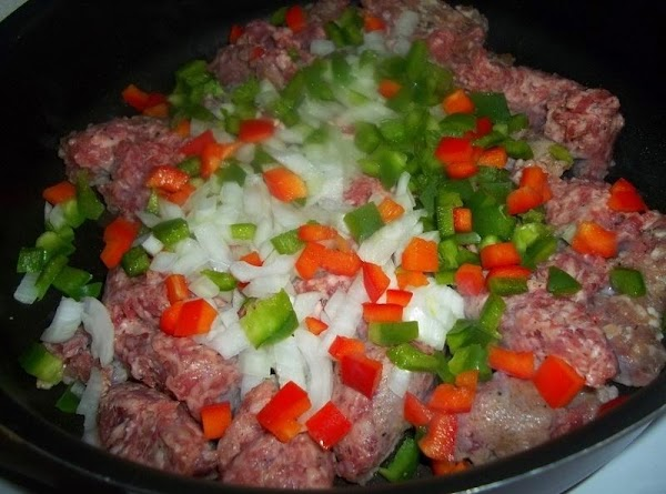 In a large skillet, brown sausage, peppers and onions, until sausage is no longer...