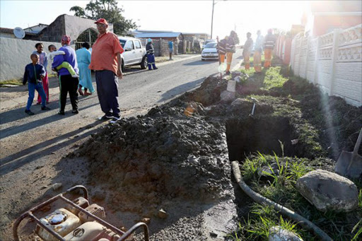 DESPERATE: Buffalo Flats resident Errol de Klerk, foreground, with members of the community outside his house where a burst pipe has left some houses without water Picture: MARK ANDREWS
