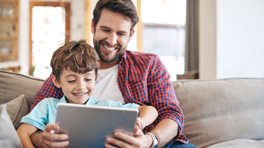 un hombre y un niño sonriendo juntos a un tablet