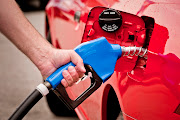 Hand Holding Blue Nozzle Pumping petrol Into Red Vehicle