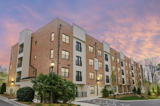 Exterior of apartment building with red brick and tan accents with black metal railings at sunset