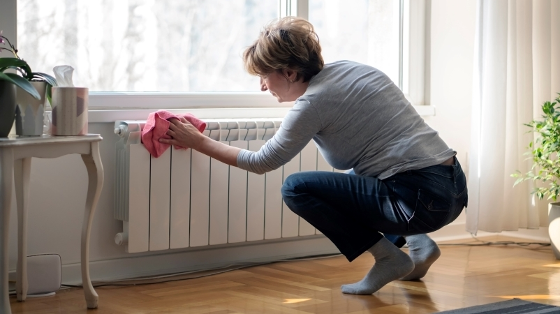 a woman cleaning the radiator in her apartment before moving out
