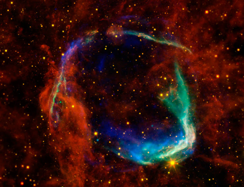 """Photo: This image combines data from four different space telescopes to create a multi-wavelength view of all that remains of the oldest documented example of a supernova, called RCW 86. The Chinese witnessed the event in 185 A.D., documenting a mysterious """"guest star"""" that remained in the sky for eight months. X-ray images from the European Space Agency's XMM-Newton Observatory and NASA's Chandra X-ray Observatory are combined to form the blue and green colors in the image. The X-rays show the interstellar gas that has been heated to millions of degrees by the passage of the shock wave from the supernova. Infrared data from NASA's Spitzer Space Telescope, as well as NASA's Wide-Field Infrared Survey Explorer (WISE) are shown in yellow and red, and reveal dust radiating at a temperature of several hundred degrees below zero, warm by comparison to normal dust in our Milky Way galaxy.By studying the X-ray and infrared data together, astronomers were able to determine that the cause of the explosion witnessed nearly 2,000 years ago was a Type Ia supernova, in which an otherwise-stable white dwarf, or dead star, was pushed beyond the brink of stability when a companion star dumped material onto it. Furthermore, scientists used the data to solve another mystery surrounding the remnant -- how it got to be so large in such a short amount of time. By blowing a wind prior to exploding, the white dwarf was able to clear out a huge """"cavity,"""" a region of very low-density surrounding the system. The explosion into this cavity was able to expand much faster than it otherwise would have.This is the first time that this type of cavity has been seen around a white dwarf system prior to explosion. Scientists say the results may have significant implications for theories of white-dwarf binary systems and Type Ia supernovae.RCW 86 is approximately 8,000 light-years away. At about 85 light-years in diameter, it occupies a region of the sky in the southern constellation of Circinus that """