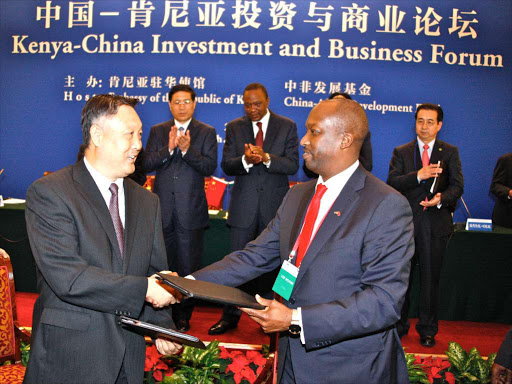 President Uhuru Kenyatta and president of China Development Bank, Zheng Zhijie witness the exchange of the MOU between Kenya National Chamber of Commerce and Industry National Chairman Kiprono Kittony and his counterpart from China Chamber of Commerce Machinery and Electronics after the signing ceremony during the Kenya-China Investment and Business Forum meeting in Beijing in August, 2013.