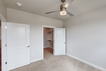 Bedroom with plush carpet, ceiling fan, neutral colored walls, and access to the closet area
