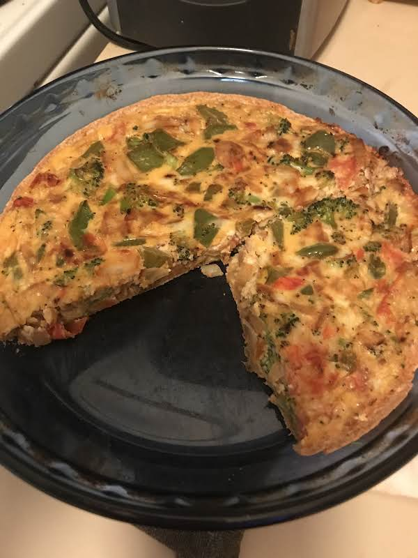 Breakfast Quiche In Pie Pan With One Slice Removed.