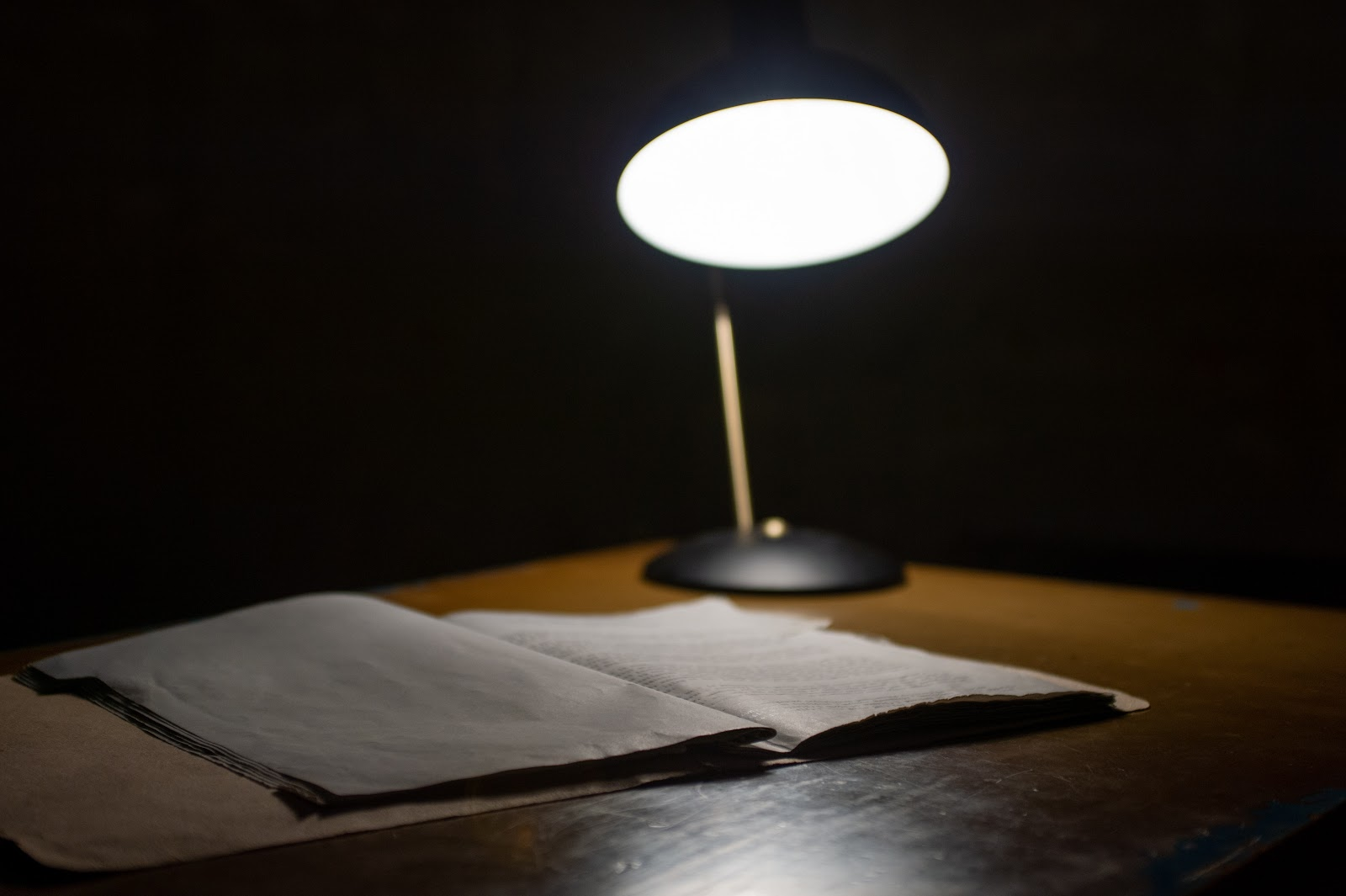 Dark room with open notebook on table underneath bright lamp