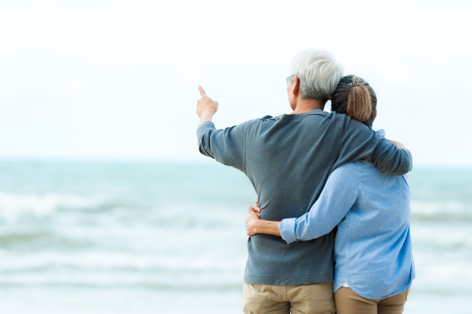 A couple looks out at the ocean during retirement