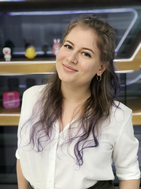 Mulher branca sorrindo para a câmera com o cabelo meio preso da cor castanho escuro.