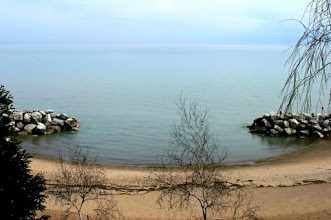 Photo: Sandy beach with rocks overlooking expansive lake