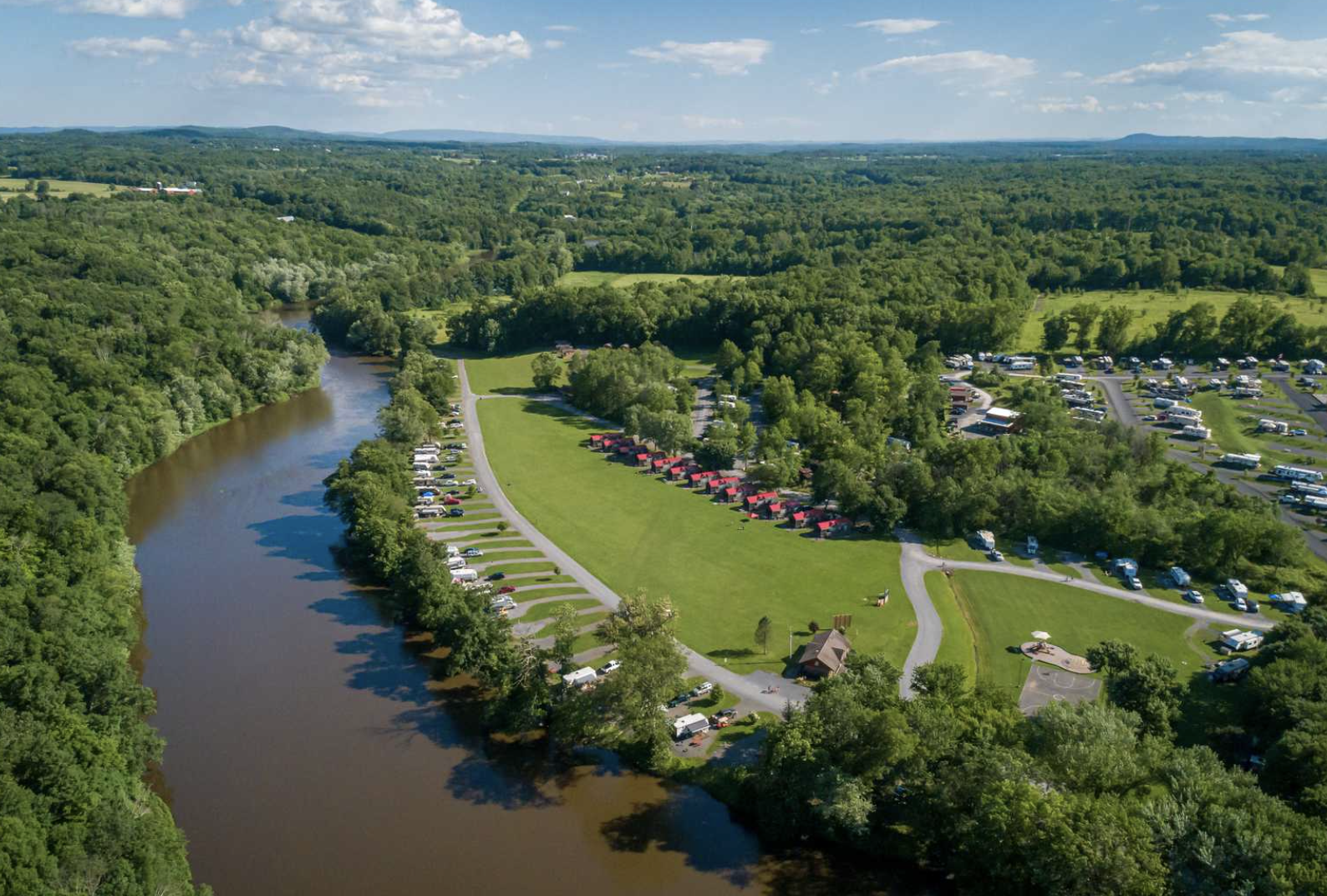 Aerial view of campground next to river with RVs and cabins in the distance
