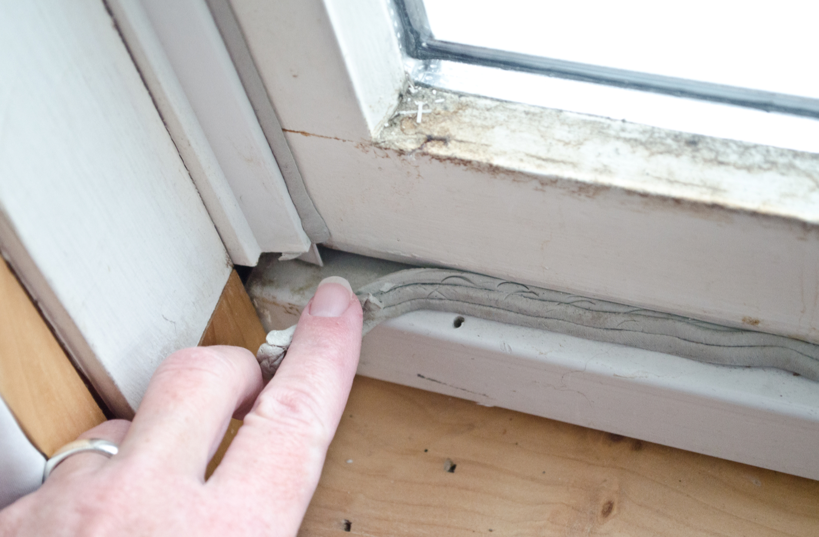 wWoman's hand pulling back loose caulking causing heat loss