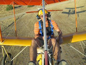Photo: Pursued by my shadow, the engine and runway are hidden behind me as I climb away from a dirt strip takeoff. I started off on the ground at a point just behind the top of my helmet.  My left hand is on the throttle lever at the full power position. I try not to use full power for more than 30 seconds to keep from over heating my little engine. The horizontal tail planes are a little twisty looking, the way they were built, functional if not beautiful. [June 2013]