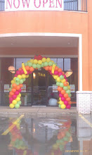 Photo: Tutti Fruitti Grand Opening garland arch with small sculptures of bananas, strawberry, oranges, apples