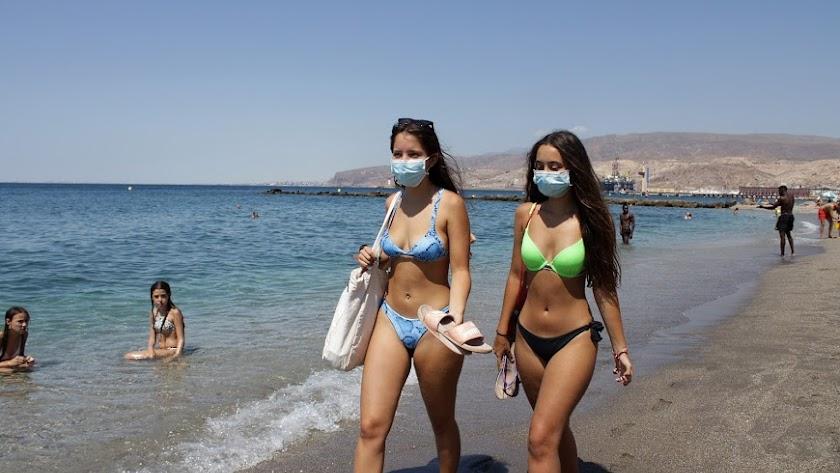 Jóvenes almerienses con mascarilla en la playa.