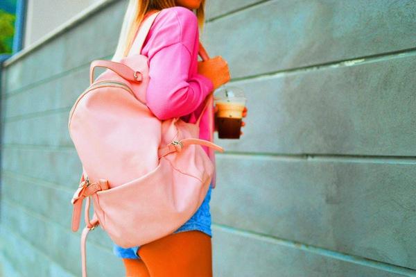 foto do corpo de uma mulher branca focando na mochila rosa e no café que ela está segurando